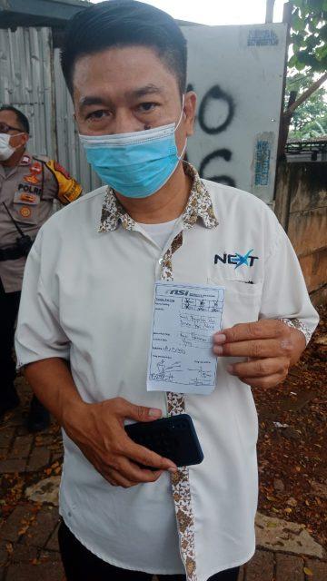 Koordinator aksi Budi H saat memegang bukti tanda terima surat tuntutan aksi ke pihak perusahaan Next Taksi